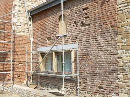 Plusieurs briques étaient cassées suites aux éclats de tirs pendant la guerre. Nous avons enlevé les briques cassées et remplacé les linteaux de béton des fenêtres par de nouveaux linteaux en pierres de taille.